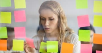 View through glass young businesswoman attaching to wall colorful post-it lot of stickers with tasks to-do list